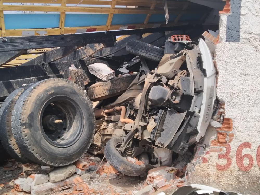 Caminhão fica sem freio e amassa carro contra garagem; pai e filho ficam feridos